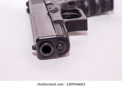 A black 9mm pistol laying on it's side on a white background