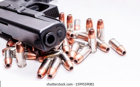 A black 9mm pistol laying on top of 9mm hollow point bullets on a white background