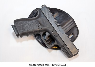 A black 9mm pistol laying in top of a black holster with a white background