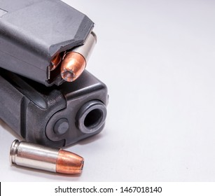 A black 9mm pistol with a loaded magazine on top of it and a single 9mm hollow point bullet next to it on a white background
