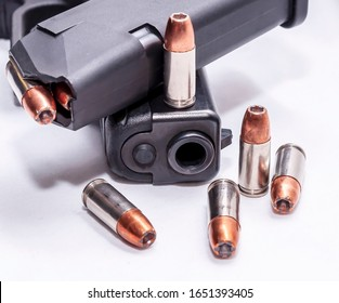 A black 9mm pistol with a pistol magazine loaded with 9mm hollow point bullets on top of it and five extra bullets on and around the gun on a white background