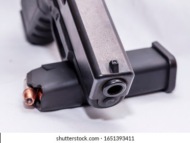 A black 9mm pistol with a pistol magazine loaded with 9mm hollow point bullets on a white background
