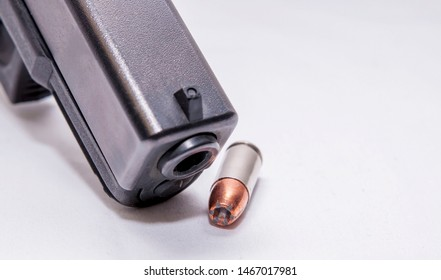 A black 9mm pistol muzzle with a single 9mm hollow point bullet next to it on a white background