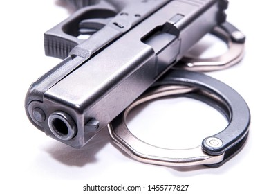 A black 9mm pistol on top of a set of black and silver handcuffs on a white background