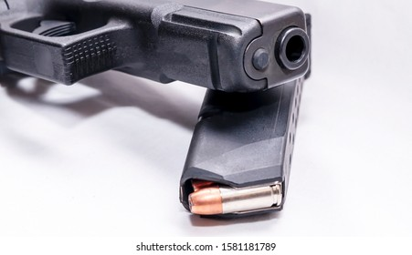 A black 9mm pistol on top of a pistol magazine loaded with hollow point bullets on a white background