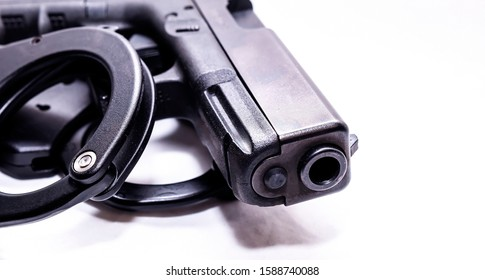 A black 9mm pistol with a set of black handcuffs next to it on a white background