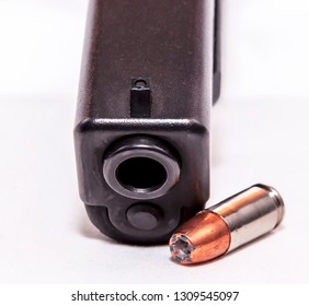 A black 9mm pistol shown with a single 9mm bullet on a white background