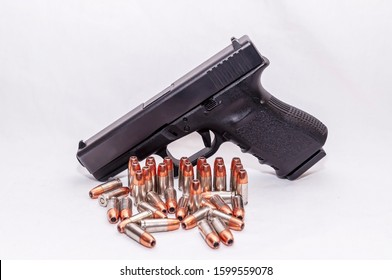A black 9mm pistol standing behind a group of 9mm hollow point bullets on a white background