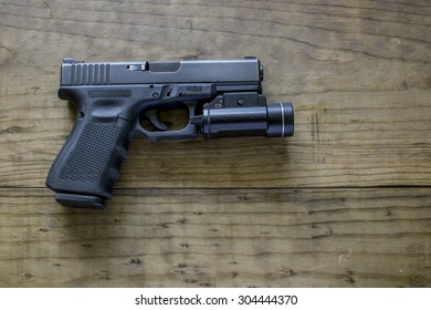 Black 9mm Pistol and Tactical Light