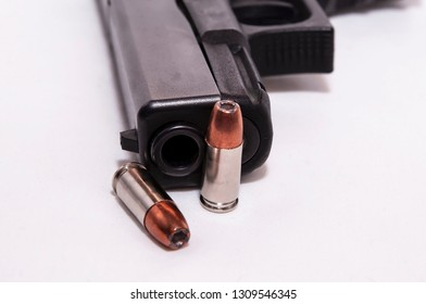 A black 9mm pistol with two 9mm hollow point bullets laying in front of it on a white background