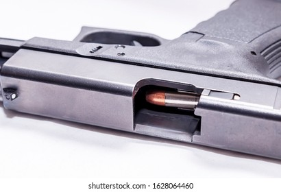 A black 9mm semi automatic pistol on it's side with an opened slide showing a 9mm bullet through the ejection port on a white background