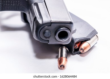 A black 9mm semi automatic pistol with a loaded pistol magazine with a single 9mm hollow point bullet on a white background