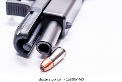 A black 9mm semi automatic with it's slide opened showing the barrel with a single 9mm hollow point bullet next to it on a white background