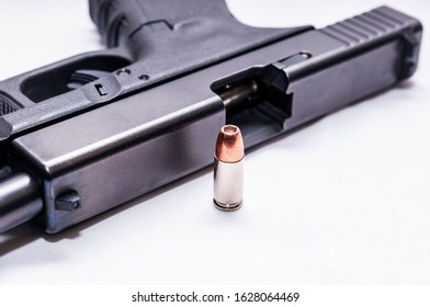 A black 9mm semi automatic with it's slide opened with a single 9mm hollow point bullet next to it on a white background