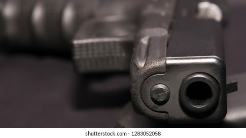 A black 9mm semiautomatic pistol laying in it's side on a black background