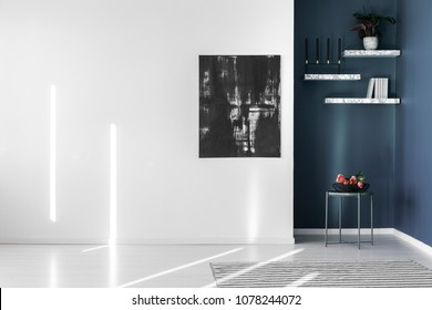 Black, abstract painting on an empty, white wall and marble shelves in a corner of a contemporary, minimalist apartment interior