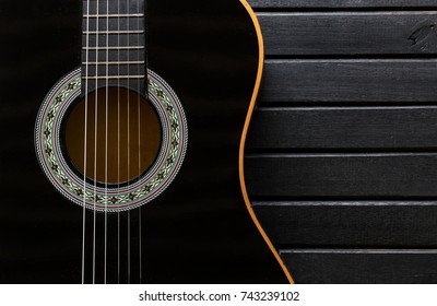 Black Acoustic Guitar body closeup, vertical, on a black wood table background, with lots of texture, showing the guitar shape and copy space
