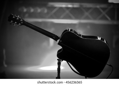 Black acoustic guitar on the stage with soffits light