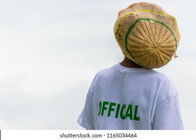 Black adult male Rasta man with locks in rasta tam, wearing white t-shirt marked Official at athletic event