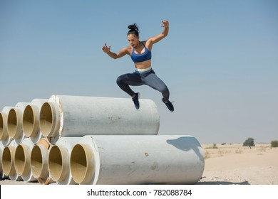 Black African American athletic woman jumps over and leaps from construction pipes wearing sports outfit in a parkour or extreme fitness competition wearing a sports outfit.