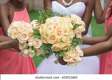 Black African american bride and bridesmaids holding bouquets of peach colored roses closeup wearing pink coral dresses no faces group photo