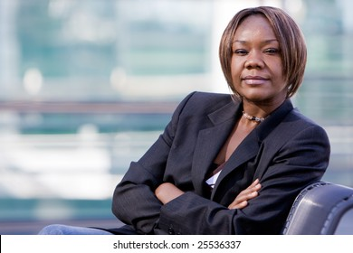 Black african american business woman posing in front of a modern office building with arms folded