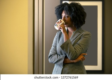 Black African American businesswoman having coffee in the morning while looking out the office window. The woman looks like she is about to start work or is taking a break.