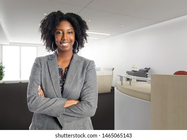 Black African American businesswoman in an office looking confident or arrogant.  She is an owner or an executive of the workplace.  Depicts careers and startup business.