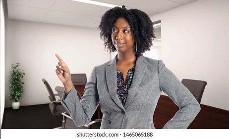 Black African American businesswoman in an office advertising or presenting something.  She is an owner or an executive of the workplace.  Depicts careers and startup business.
