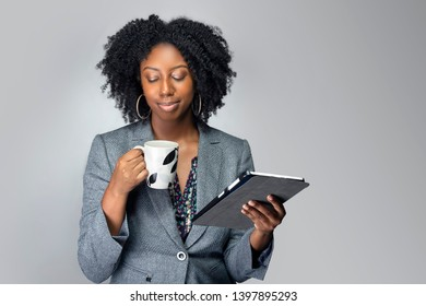 Black African American businesswoman or writer as a keynote speaker for a seminar preparing for the presentation with a tablet and coffee.