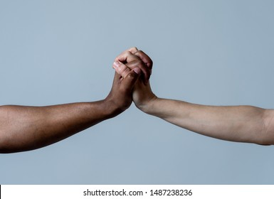 Black African American and Caucasian hands holding together stop racism. White and black skin arms in world unity multiracial love and understanding in tolerance and races diversity cooperation.