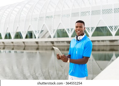 Black, African American college student wearing headphones and listening to music on a digital tablet computer