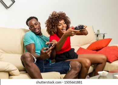 Schwarzafrikanisches Ehepaar mit Spaß beim Spielen von Videospielen