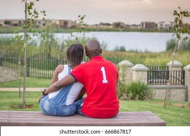 Black african american couple sitting on park bench looking at lake holding each other
