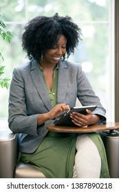Black African American female as an adult student taking an online course and browsing with a tablet.  She is taking online school or doing research as a businesswoman.