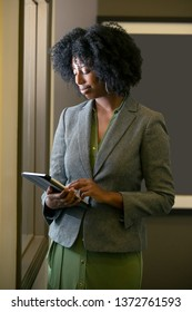 Black African American female businesswoman making a business plan with a tablet.  She is using the digital device via wifi in the office. Also depicts adult school with modern technology.