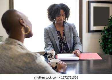 Black African American female client looking worried while applying for a loan or employment.  Also depicts a businesswoman in a meeting or a job review with a manager.