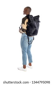 Black African American female wearing a backpack looking at white background for composites.  She is standiing like she is a tourist or a hiker trekking.