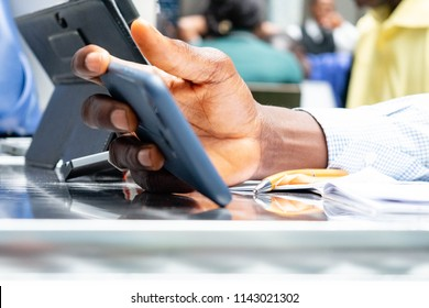 Black African American man's hand holding smartphone text message or promotional content, or watching video on mobile phone outdoors for fast internet or cellular network connection concept