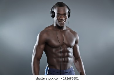 Black african american muscled fitness man with headphones listening to music. Wearing blue shorts. Studio shot against grey.