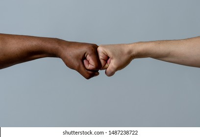 Black African American race male and white Caucasian woman hands giving a fist bump in agreement partnership and cooperation multiracial diversity and immigration concept. Stop racism campaign.