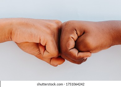 Black African American race male and white Caucasian woman hands giving a fist bump in agreement partnership and cooperation multiracial diversity and immigration concept. Stop racism concept