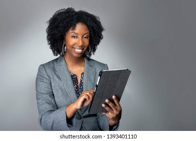 Black African American teacher or businesswoman sitting and holding a tablet computer.  The confident female author or writer looks like she is preparing for a seminar or as a keynote speaker.