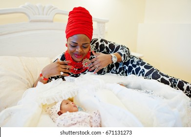 Black african american woman dressed in traditional ethnic clothes laying next to her small twins babies on the bed.
