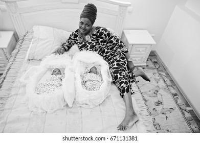 Black african american woman dressed in traditional ethnic clothes laying next to her small babies twins on the bed. Black and white photo.