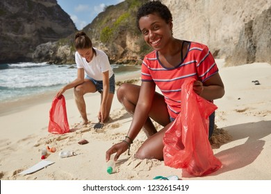 Black African American woman and her companion pick up recyclable plastic bottles and other rubbish, involved in volunteer work, pose at beach, being environmentally friendly. Cleaning concept