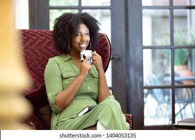 Black African American woman resting at home drinking coffee or CBD tea while relaxing on a chair.  She is holding a warm cup in a living room.