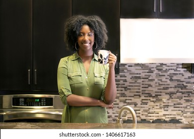 Black African American woman resting at home drinking coffee or CBD tea while standing in a kitchen