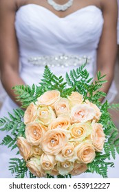 Black African bride in white wedding dress holding bouquet of peach colored roses and green leaves with diamond necklace