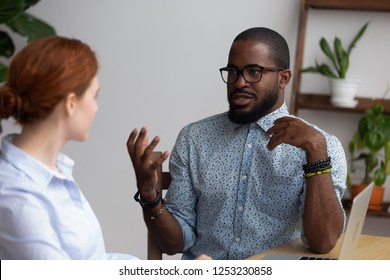 Black african company member presenting sharing his thoughts creative ideas to executive manager sitting together in office room. Diverse workmates talking having friendly relations have busy workday